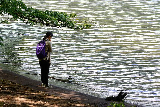 芦ノ湖に一人静かに御供(ごく)をまく女性